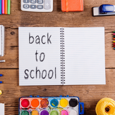 """Les tradicions del primer dia. inlingua Andorra blog post notebook with the words """"back to school"""" scribbled on it surrounded by calculator, colors and a stabler on a desk."""