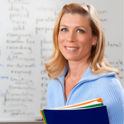Woman teacher in front of white board with book in hand. inlingua Andorra