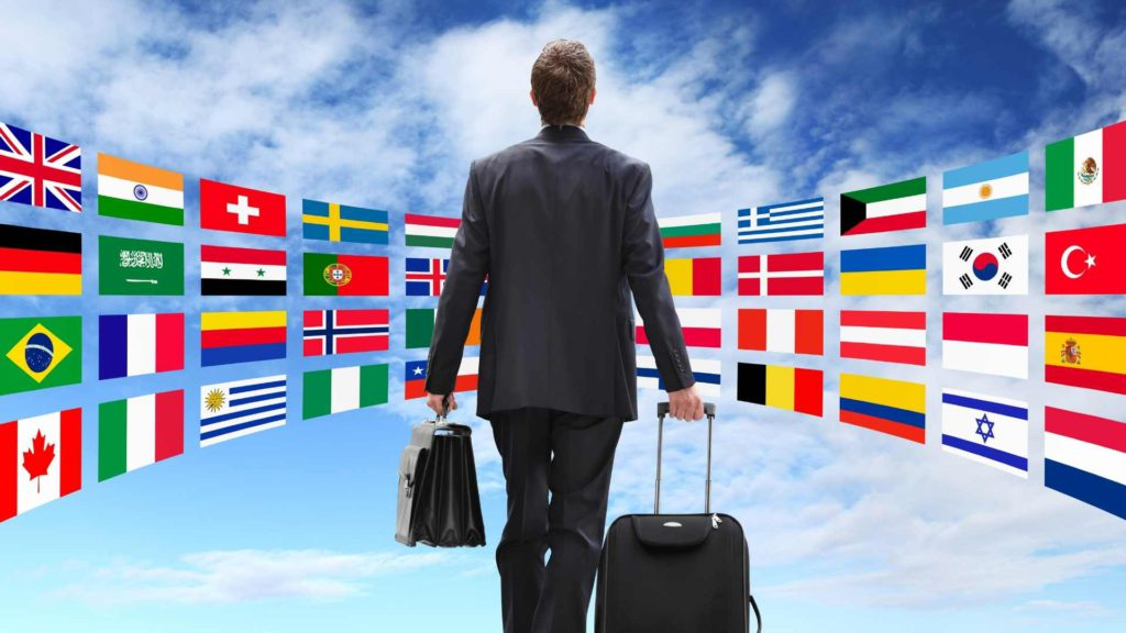 inlingua Andorra student learning new languages in Andorra and traveling abroad. Man with suitcase in front of many different flags